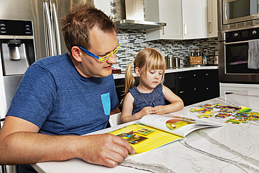 A father sitting down with his young daughter in the kitchen to read a book: Edmonton, Alberta, Canada