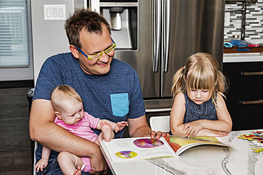 A father sitting down with his daughter in the kitchen to read a book and build a puzzle while holding his baby in his lap: Edmonton, Alberta, Canada