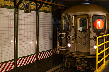 Subway underground on tracks beside tiled wall, Manhattan; New York City, New York, United States of America