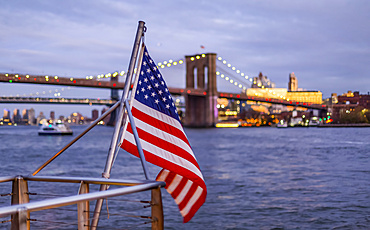 An American Flag flies from a railing at the waterfront with a view of the Brooklyn Bridge, Manhattan; New York City, New York, United States of America