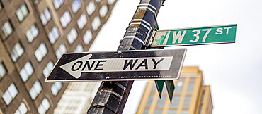 Street signs on a post, a directional one way and West 37th Street, Manhattan; New York City, New York, United States of America
