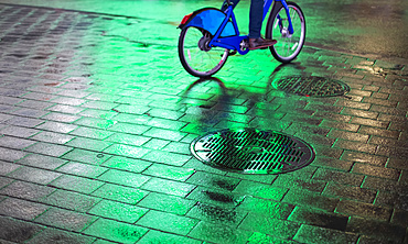 Cyclist riding bike on wet walkway with glowing green light at night in Manhattan; New York City, New York, United States of America