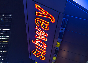 Subway sign illuminated at night in Manhattan; New York City, New York, United States of America