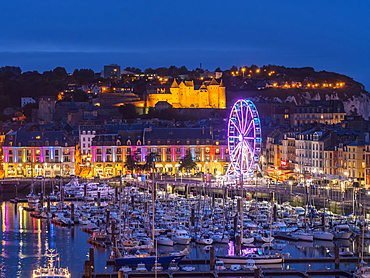 Harbour full of boats and an illuminated ferris wheel at night with lights illuminating the Chateau de Dieppe castle on the hillside; Dieppe, Normandy, France
