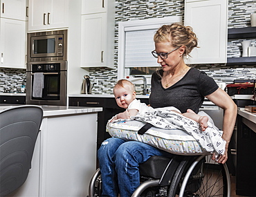 A paraplegic mother holding her baby on her lap, in her kitchen, while pushing in her wheel chair: Edmonton, Alberta, Canada