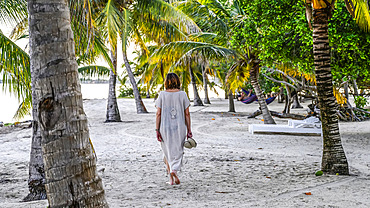 A mature woman walks on the white sand among the palm trees on a beach in the Caribbean, Placencia Peninsula; Belize