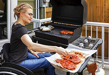 A paraplegic woman cooking steaks and baked potatoes on an outdoor barbecue while sitting in her wheelchair: Edmonton, Alberta, Canada