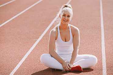 Woman sits on a lane of a running track; Wellington, New Zealand