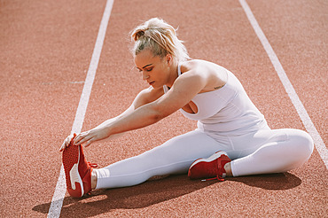 Woman sits to stretch her leg muscles to prepare for running on a track; Wellington, New Zealand
