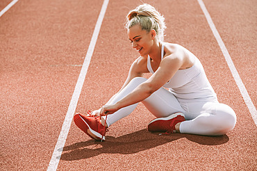Woman ties her shoelace to prepare for running on a track; Wellington, New Zealand