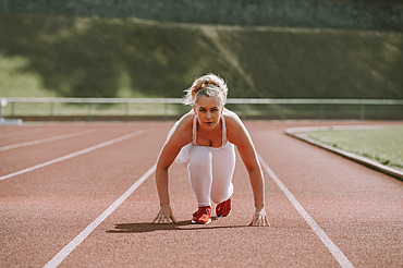 Woman in a starting position for running on a track; Wellington, New Zealand