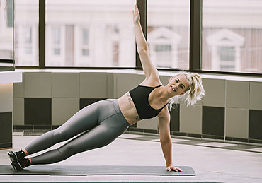 Woman working out on a mat doing a side plank; Wellington, New Zealand