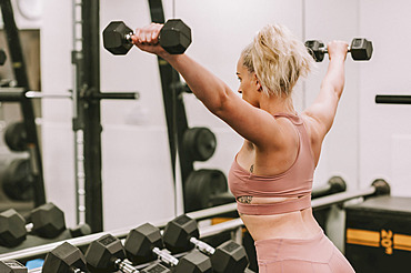 Woman working out with weights; Wellington, New Zealand