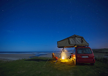 Car with roof tent camping by Falcarragh Beach at night; County Donegal, Ireland
