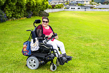 Maori woman with Cerebral Palsy in a wheelchair on a grass field in a park area; Wellington, New Zealand