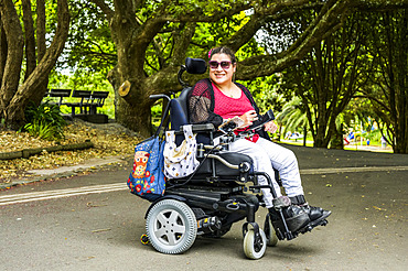 Maori woman with Cerebral Palsy in a wheelchair in a park area; Wellington, New Zealand
