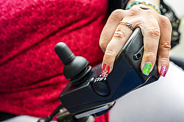 Maori woman with Cerebral Palsy in an electric wheelchair with a joystick and controllers, fingernails showing nail art; Wellington, New Zealand