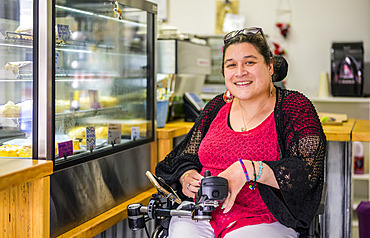 Maori woman with Cerebral Palsy in a wheelchair in a cafeteria; Wellington, New Zealand
