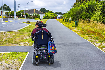 Maori woman with Cerebral Palsy in a wheelchair going down a sidewalk; Wellington, New Zealand