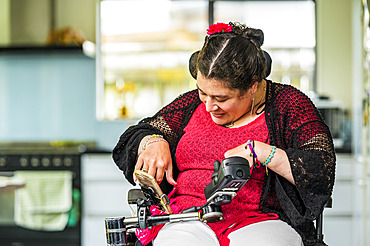 Maori woman with Cerebral Palsy in a wheelchair using a smart phone; Wellington, New Zealand