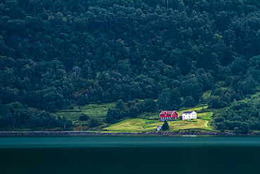 Isolated Norwegian house by a lake, surrounded by a dark forest; Norway