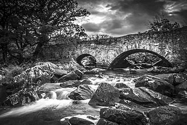 Black and white image of an arched stone bridge over a flowing river; County Kerry, Ireland
