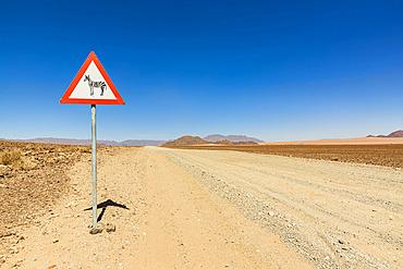 Attention wild animals sign on a long dry road, Namib Desert, Namib-Naukluft National Park; Namibia