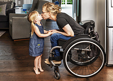 A young girl standing on her tippy-toes to give a kiss to her paraplegic mom who is in a wheelchair: Edmonton, Alberta, Canada.