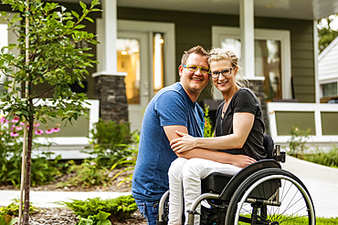 A husband and his paraplegic wife posing for a family photo in their front yard on a warm fall day: Edmonton, Alberta, Canada