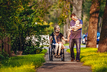 A family out walking in the evening and the mother is a paraplegic in a wheelchair; Edmonton, Alberta, Canada