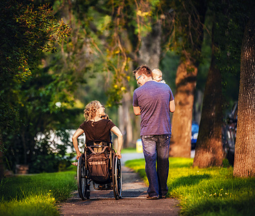 A view from behind of a family out walking in the evening and the mother is a paraplegic in a wheelchair; Edmonton, Alberta, Canada