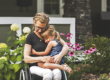 A paraplegic mom holding her little girl in her lap while sitting in her wheelchair in her front yard on a warm summer afternoon: Edmonton, Alberta, Canada.