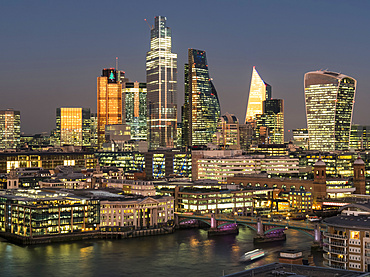 Cityscape and skyline of London at dusk with 20 Fenchurch, 22 Bishopsgate, and various other skyscrapers, and the River Thames in the foreground; London, England