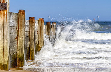 Waves splashing along the wooden wall at the shore and wind turbines in the distance in the water along the coast of Blyth; Blyth, Northumberland, England