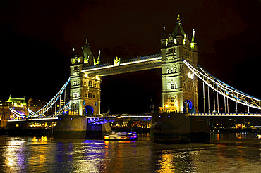 Tower Bridge illuminated at nighttime and reflected in the tranquil water of the River Thames; London, England