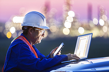 Man working on a laptop and smart phone with an oil refinery in the background; Alberta, Canada