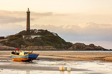 Colourful fishing boat tied to the beach and a lighthouse on a hill along the coast, Ke Ga Cape; Ke Ga, Vietnam