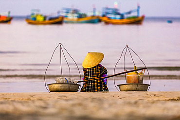 A woman sits on the beach looking out to the numerous fishing boats in the water off the coast, Ke Ga Cape; Ke Ga Island, Vietnam
