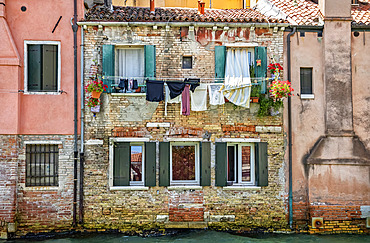 Clothesline and a residential building along a canal; Venice, Italy