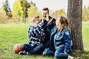 A young man with Down Syndrome celebrates with a high-5 after winning a game on his pad while enjoying quality time with his father and mother in a city park on a warm fall evening; Edmonton, Alberta, Canada