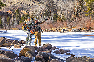 Hunters with camouflage clothing and rifle looking out with binoculars; Denver, Colorado, United States of America