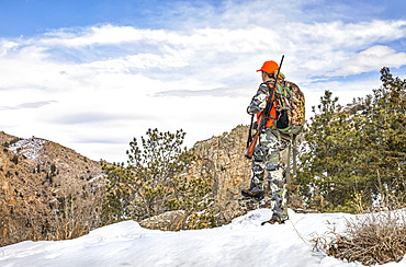 Hunter with camouflage clothing and rifle looking out in winter; Denver, Colorado, United States of America