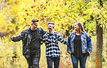 A young man with Down Syndrome walking with his father and mother while enjoying each other's company in a city park on a warm fall evening; Edmonton, Alberta, Canada