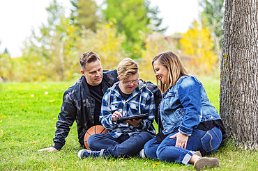 A young man with Down Syndrome learns a new program on a tablet with his father and mother while enjoying each other's company in a city park on a warm fall evening; Edmonton, Alberta, Canada