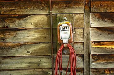 Vintage air pump with hose mounted to a wooden wall; United States of America
