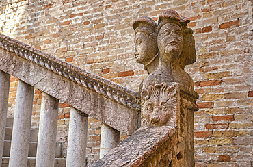 Carved stone sculpture of human heads and an animal face as a decorative post on a handrail beside a brick wall and stairway; Venice, Italy