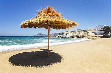 Thatch shelter casting shade onto the beach; Milos, Greece