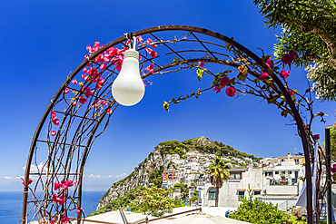 A decorative archway with light in the foreground and the city of Capri on the limestone crag along the coast of the Mediterranean; Capri, Italy