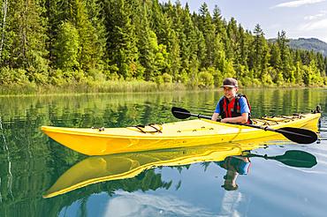 A teenage boy kayaking on White Lake, White Lake Provincial Park; British Columbia, Canada
