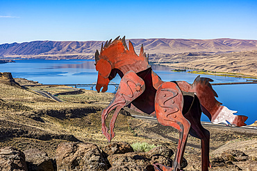 Metal art depicting wild horses running across a ridge atop the Wild Horse Monument near the town of Vantage in Eastern Washington. Wanapum Lake formed by a dam on the Columbia River and the I-90 Bridge in the background; Vantage, Washington, United States of America